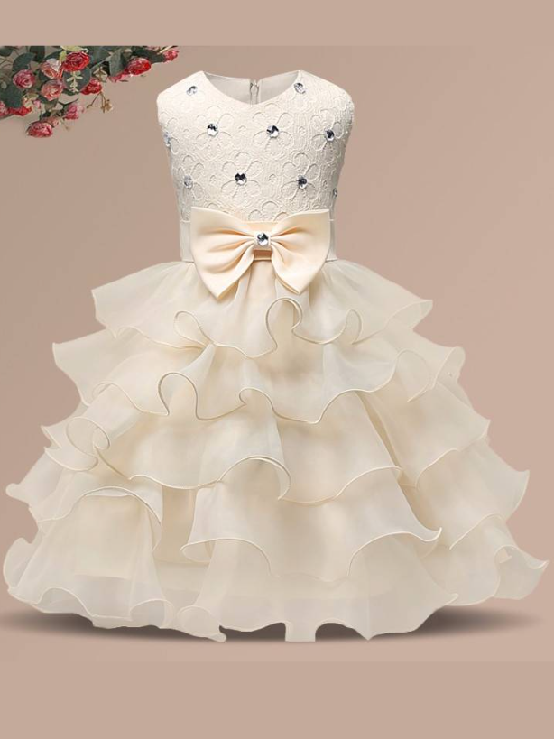 Baby princess dress has a floral lace bodice with rhinestone details, a bow belt at the waist, and a multi-layered tulle skirt-creme