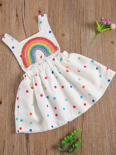 Baby white dress has a colorful polka dot print and rainbow applique pullover style ties at the back