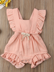 Baby bohemian Overall style romper onesie that ties in the back and has a drawstring at the waist. Little ruffled adorn the shoulder and short hem pink