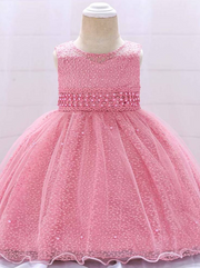 Baby dress has a tulle overlay with embroidered stars with an attached pearl belt and bow at the back-pink