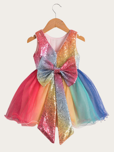 Girls dress has a sequin bodice, a tulle rainbow skirt, and a large sequin bow at the back