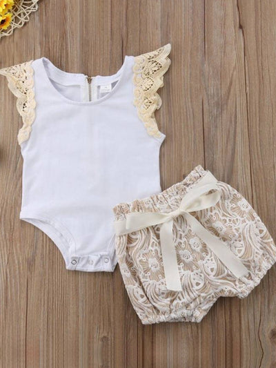 Baby set features a short-sleeved onesie with a crochet ruffle at the shoulder and embroidered shorts with a sash