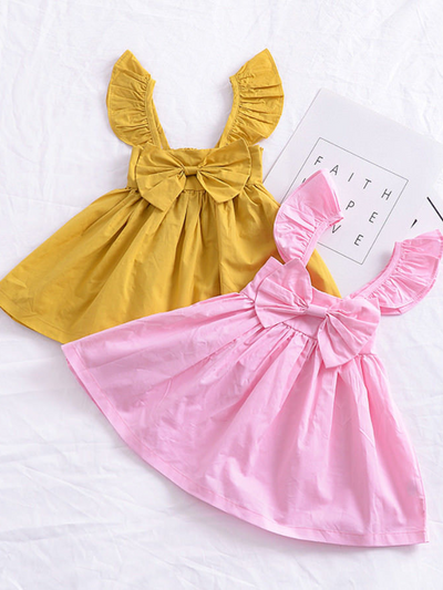 Baby apron style dress has a ruffled adjustable straps and a stretchy bodice with a big bow