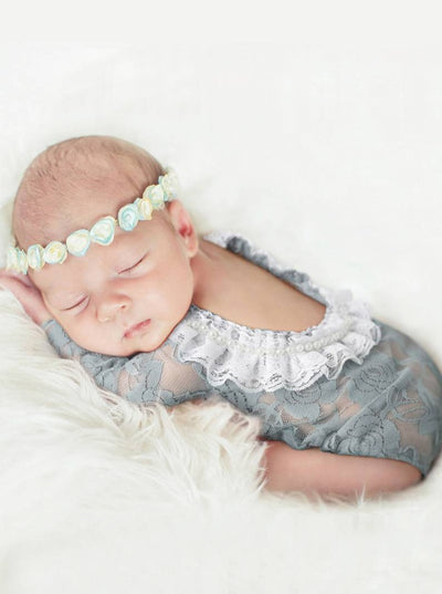 Baby  lace onesie has an open back with white lace ruffles grey
