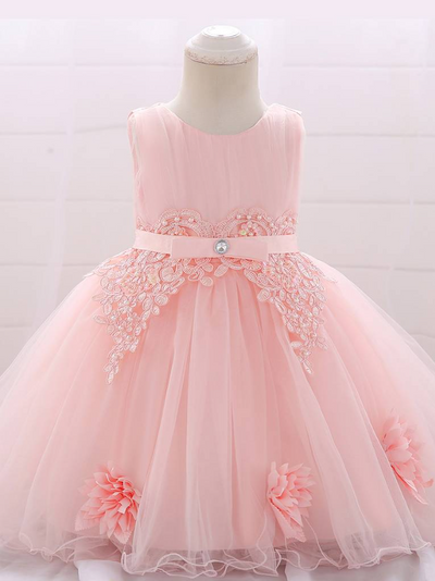Baby dress has a tulle overlay with flower applique and a satin belt with rhinestone detail-pink