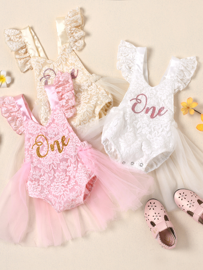"Baby lace overall onesie that ties at the back with tulle train, little ruffles at the shoulder, and a gold ""One"" printed on the bodice"
