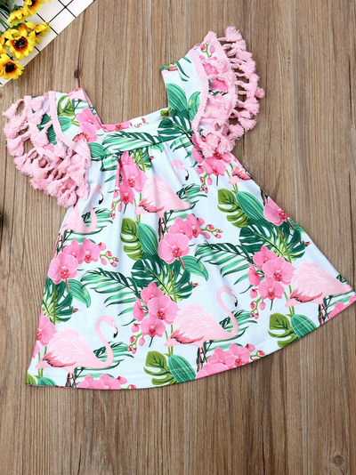 Baby apron style dress has a flamingo and tropical leaf print, a cute tasseled hem at the ruffled shoulders add a little extra-extra