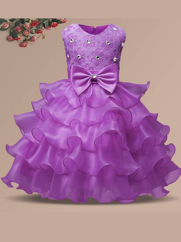 Baby princess dress has a floral lace bodice with rhinestone details, a bow belt at the waist, and a multi-layered tulle skirt-lilac