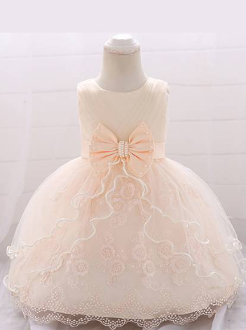 Baby dress has a tulle overlay with a multi-layer skirt, bow detail at the waist-creme