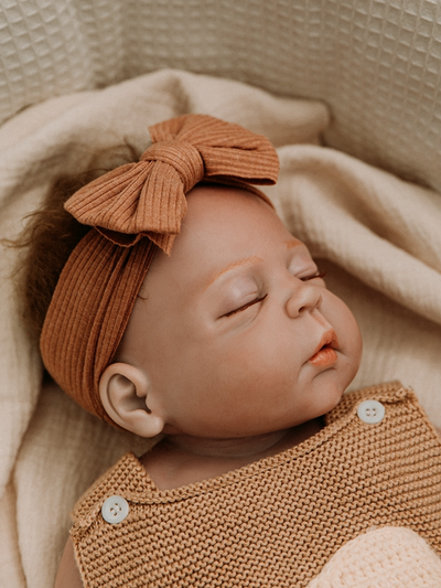 Baby wearing bow headband  brown