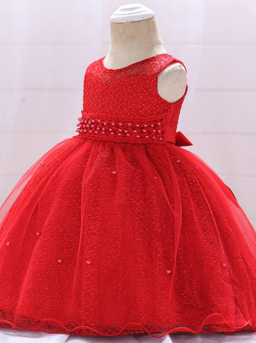 Baby dress has a tulle overlay with embroidered stars with an attached pearl belt and bow at the back-red