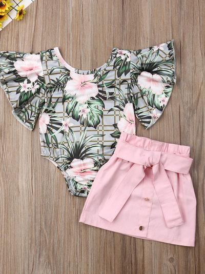Baby set has a ruffled onesie with tropical print and pink skirt with front buttons and sash