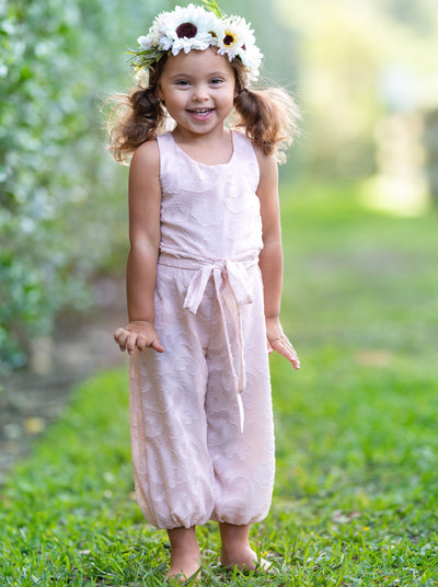 Girl smiling wearing pink lace paisley jumpsuit with belt with flower halo headband