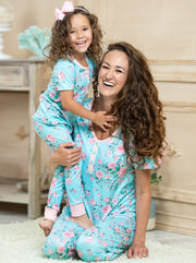short-sleeved aqua pajamas feature a pink rose print, 3 front buttons, and pink cuffs on the kid version