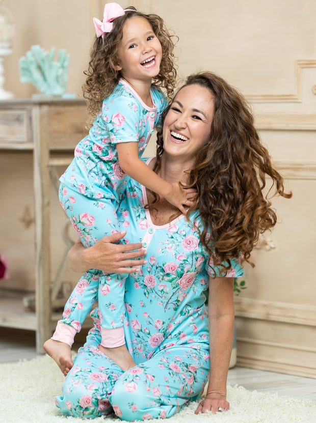 mommy and me short-sleeved aqua pajamas feature a pink rose print, 3 front buttons, and pink cuffs on the kid version