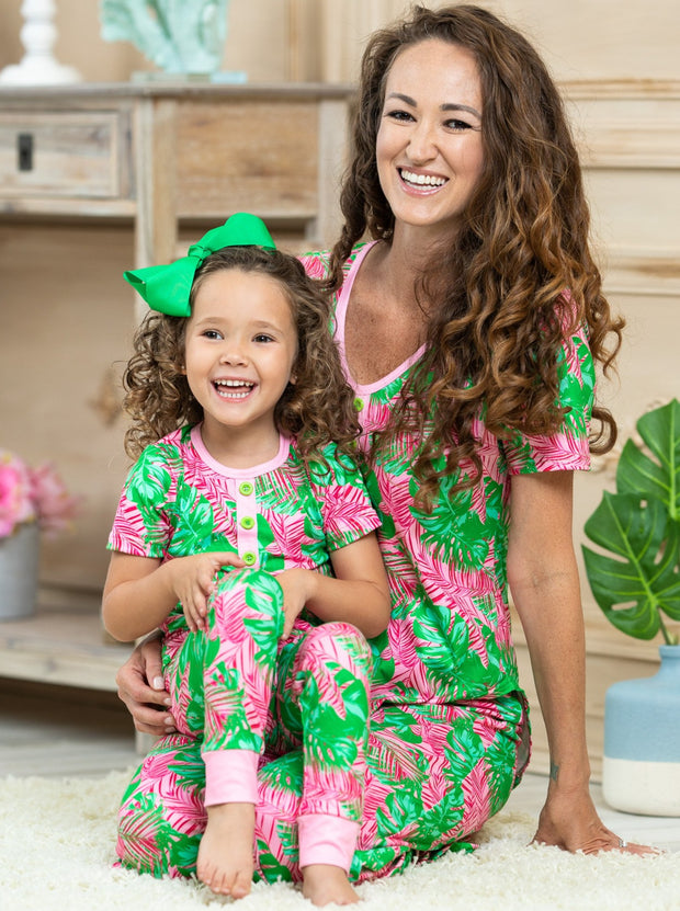 mommy and me short sleeved pink pajamas feature pink/green palm leaf prints, 3 front buttons, and pink cuffs on the kid version