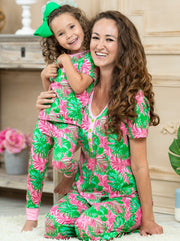 Mommy and Me short leeved pink pajamas feature pink/green palm leaf prints, 3 front buttons, and pink cuffs on the kid version