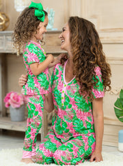 short leeved pink pajamas feature pink/green palm leaf prints, 3 front buttons, and pink cuffs on the kid version