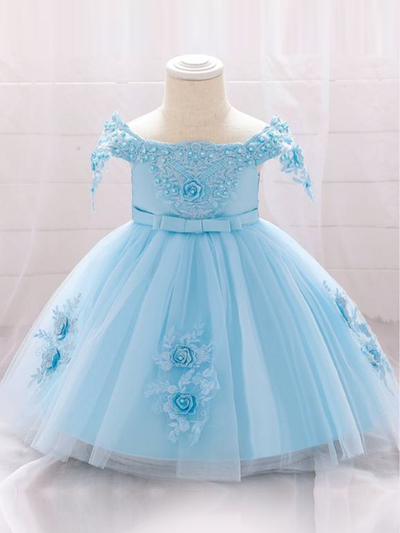 Baby dress has a satin embroidered bodice with pearl details and capped sleeves, a bow belt at the waist, and a tulle skirt with flower applique