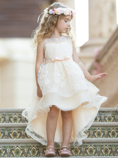 Girls hi-low and double layered dress has an embroidered bodice with pearl detail and bow belt