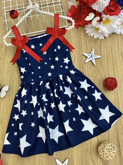 Girls blue summer dress feature a star print and has red straps with little bows