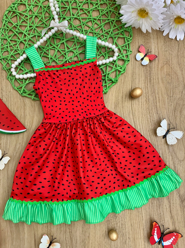 girls dress has a watermelon design. Green shoulder straps and hem with red, watermelon seeds fabric