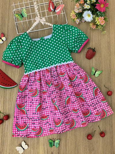 Girls dress has a green bodice with small polka dots and a checkered skirt with watermelons