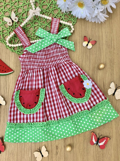 Girls dress has a stretchy bodice and skirt in a checkered print, a green with white polka dot hem, and cute watermelon pockets