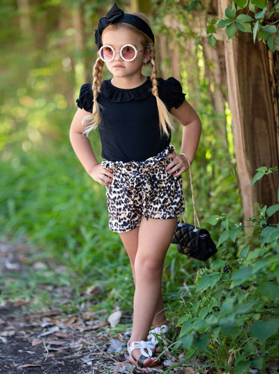 girls set features a black top with a bib and ruffled short sleeves and leopard printed shorts with a sash