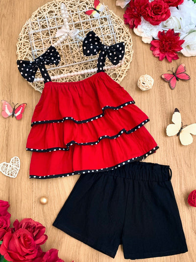 Girls set features a red top with ruffles and polka dot bows at the shoulders and black shorts with a sash