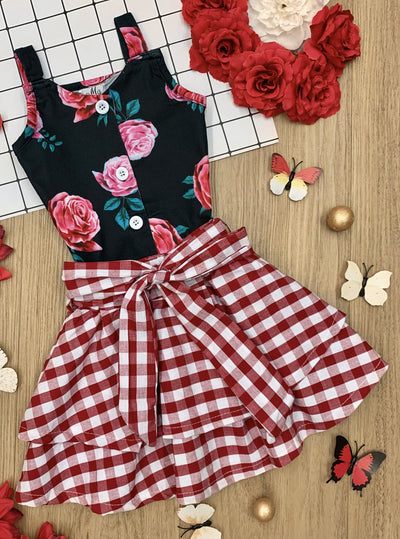 Girls set features a black floral top with front buttons and a checkered skirt with a sash at the waist