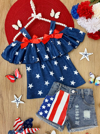 Girls set features a blue off-shoulder top with white stars with distressed denim shorts with flag patch