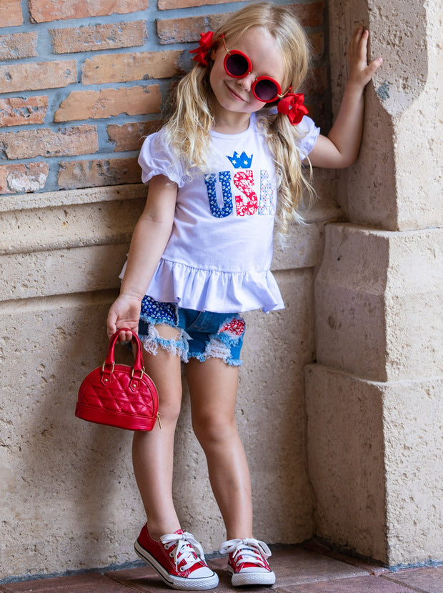 "Girls set features a white top with ""USA"" print and patched denim shorts with a red sash"