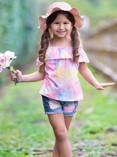 Girl wearing hat and  off shoulder tie dye top and distressed patched denim shorts holding flowers