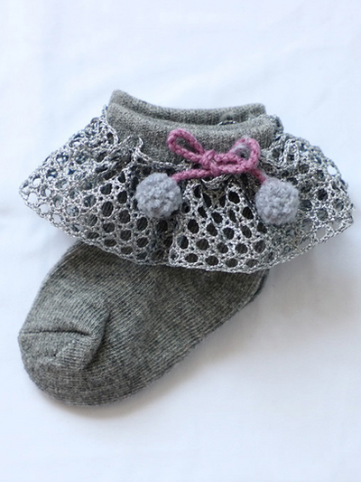 Baby socks with crochet and pompom details