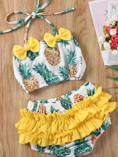 Baby swimsuit features a top with a fruit print and an adjustable halter style strap with ruffles bottoms