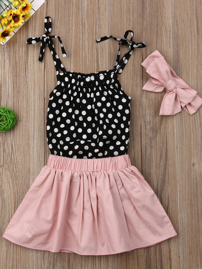 Baby set has a polka dot onesie with adjustable straps, comes with a pink skirt and matching headband