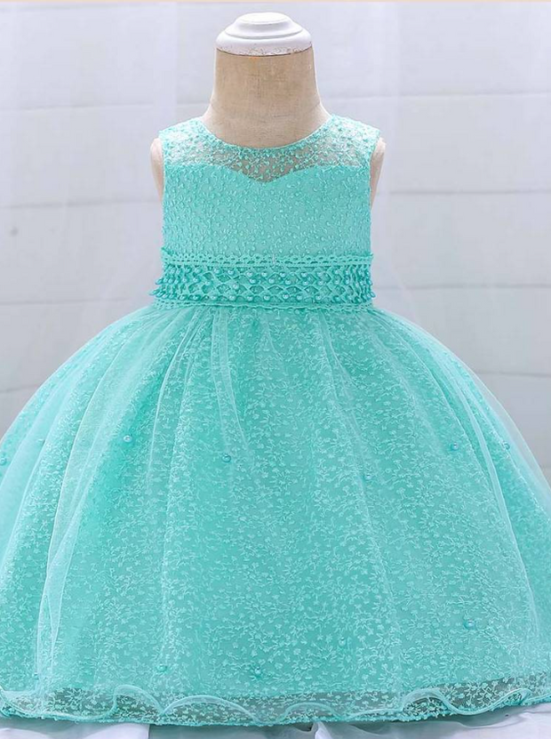Baby dress has a tulle overlay with embroidered stars with an attached pearl belt and bow at the back-turquoise