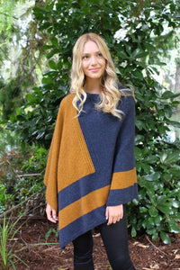 Asymmetrical possum merino poncho with geometric pattern in contrast colour. Textured knit structure feature in contrast panel. Lothlorian. Made in New Zealand. Gold