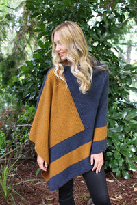 Asymmetrical possum merino poncho with geometric pattern in contrast colour. Textured knit structure feature in contrast panel. Lothlorian. Made in New Zealand.