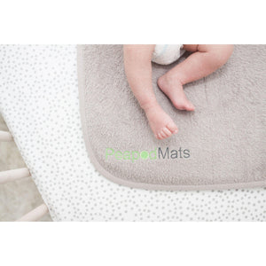 PeapodMats washable, reusable waterproof 1.5'x1.5' chair pad for bed wetting and incontinence, product illustration in sand with baby's legs kicking