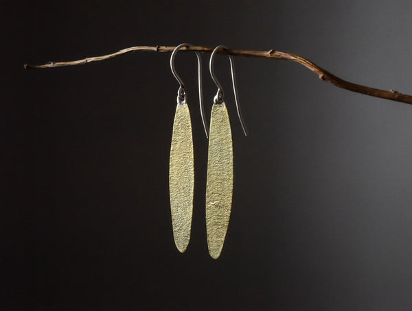 view of simple leaf brass textured earrings hanging