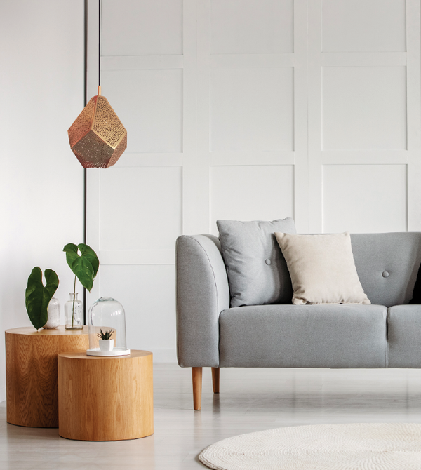 modern space wood side tables dounia home almas pendant light in copper with grey couch and wood paneling and fig leaf