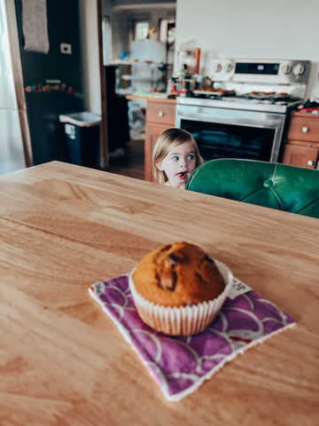 little girl with tongue out looking at muffin