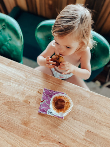 little kid eating a muffin on a green chair