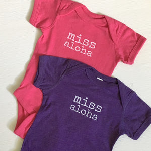 pink and purple baby girl onesie with white lettering that says miss aloha