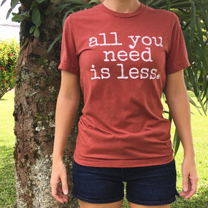 girl wearing jean shorts and gender neutral red t-shirt with white font that says all you need is less
