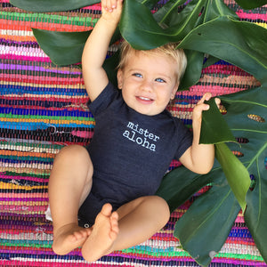 baby boy on a colored rug wearing a navy blue baby onesie with white lettering that says mister aloha