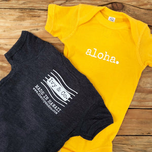 gold yellow and navy blue gender neutral baby Ivy & Co. onesie with white writing that says aloha