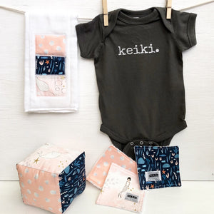 dark grey baby Ivy & Co. onesie with white lettering that says keiki hanging on a clothes line with pink burp cloth and baby soft block